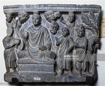 Buddha sitting under a tree with his devotees by his side